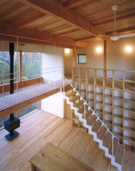 2階に浮いているブリッジへと至る階段。背後に控える開放的な飾り棚とセットでデザインされています。
