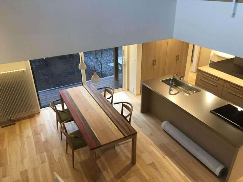 階段から見下ろす、ダイニングテーブル(無垢いろいろ樹種)、アイランドキッチン(SUSバイブレーション)、輻射暖房(パネルヒーター)